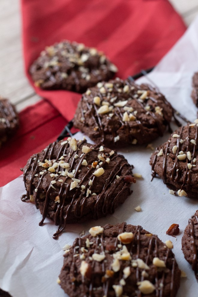 chewy chocolate hazelnut cookies with chocolate drizzle cooling on wire rack.