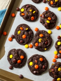 chocolate reese's pieces cookies on a cookie sheet with more reese's