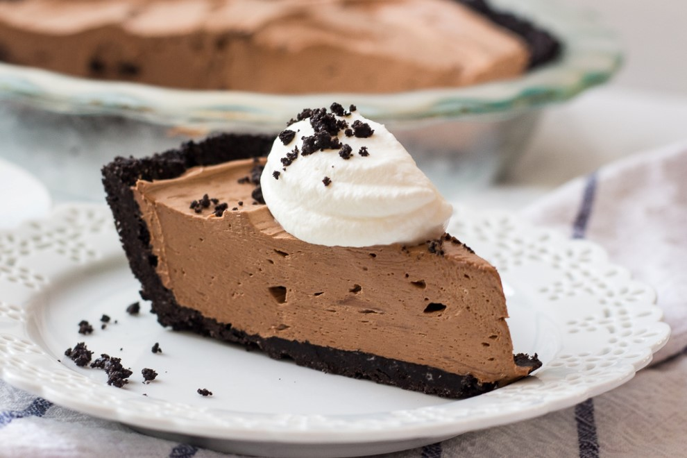 a piece of oreo nutella cheesecake with whipped cream