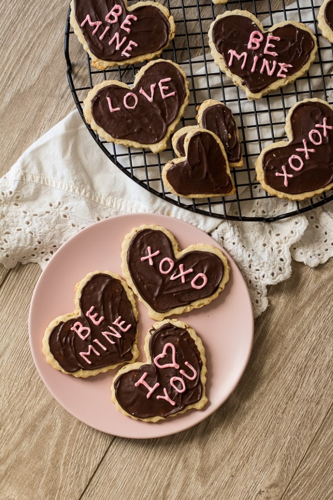 valentines day shortbread heart cookies with chocolate frosting on a pink plate