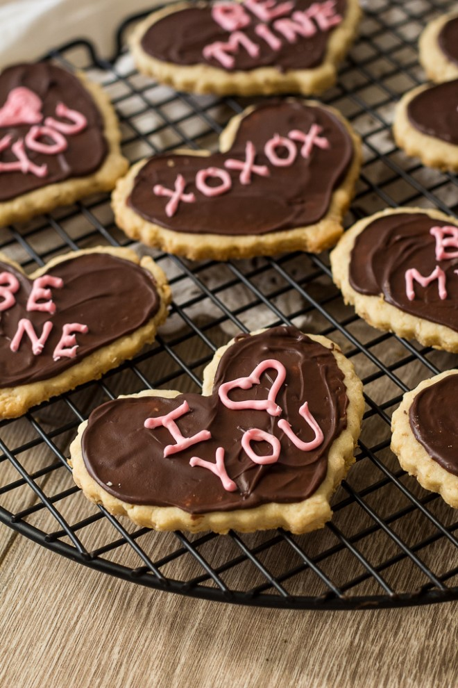 valentines day shortbread heart cookies with chocolate frosting on a cooling rack