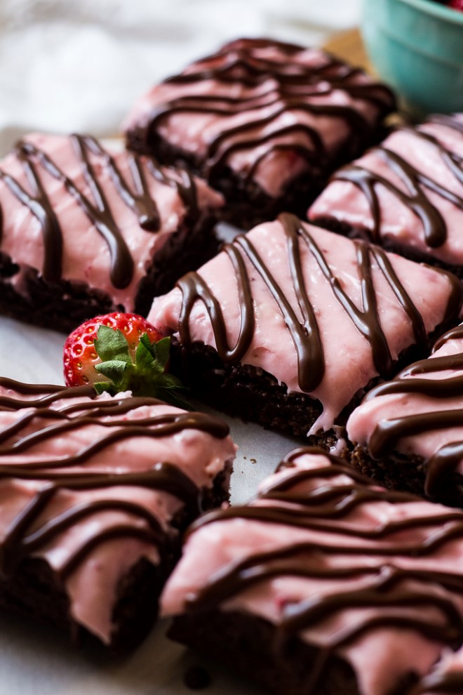 brownies with strawberry cream cheese frosting and a fudge drizzle