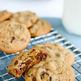 Peanut butter chocolate chip cookies on a cooling rack with a half eaten cookie beside them.