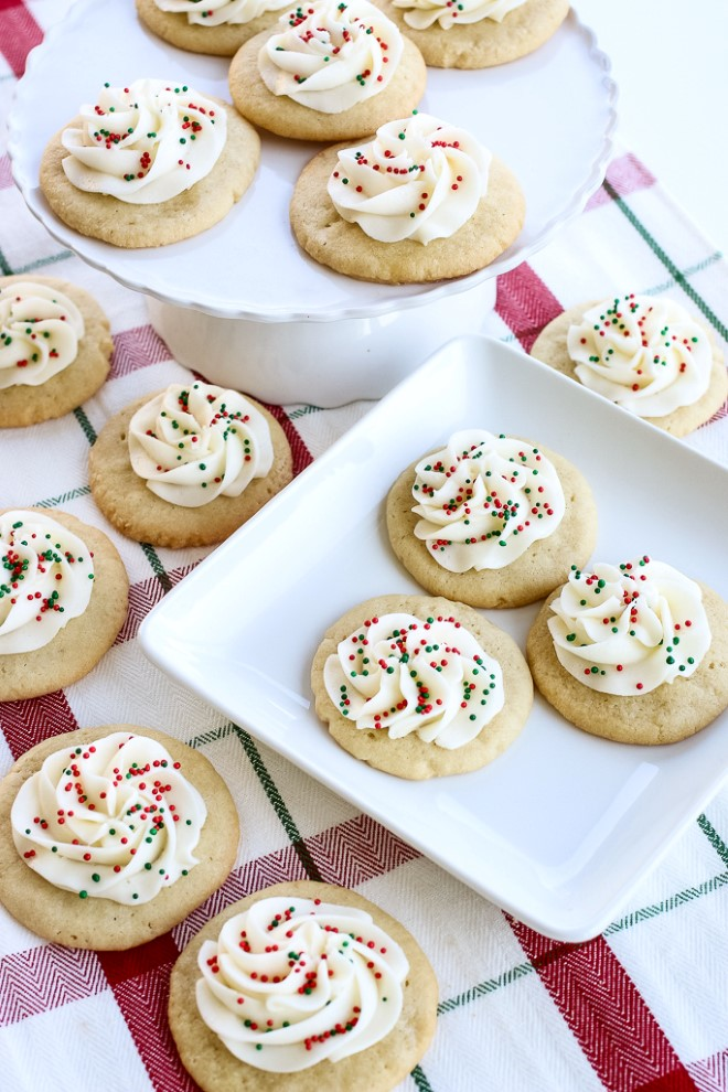 Christmas sugar cookies with white icing and sprinkles on top.