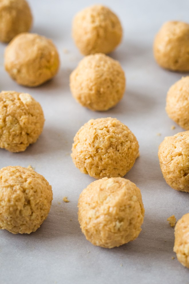 Rice Krispie balls rolled out onto parchment paper.