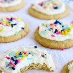 An iced sugar cookie with a bite out of it.