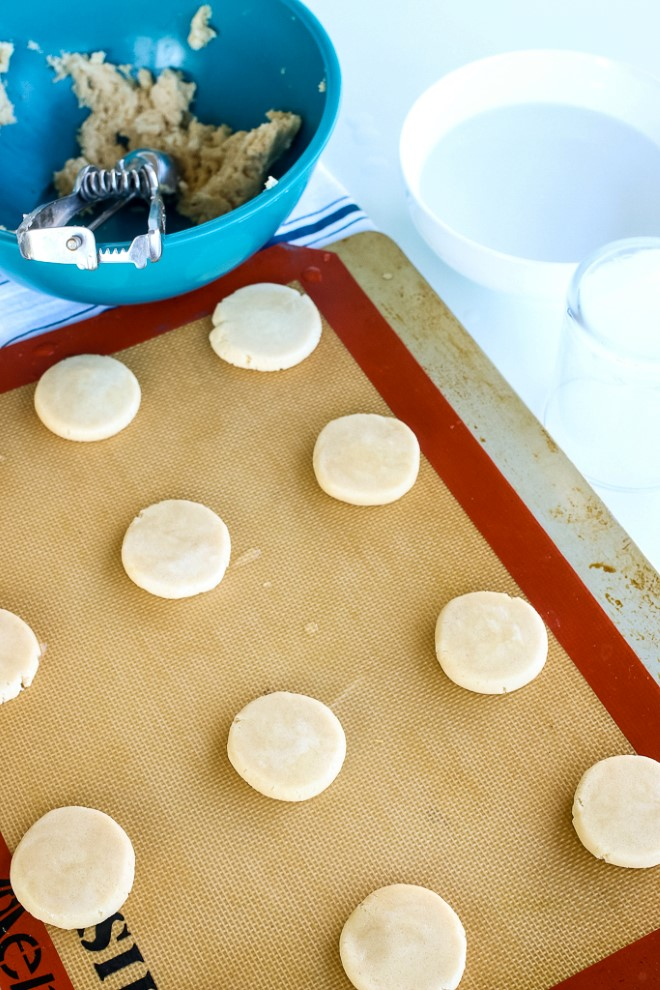 Sugar cookies on a baking sheet ready to be baked in an oven.